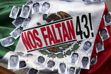 """Pictures of the missing students of Ayotzinapa College Raul Isidro Burgos and a sticker that reads """"We are missing 43"""" are seen over a Mexican flag during a march to mark the 16-month anniversary of their disappearance in Mexico City"""