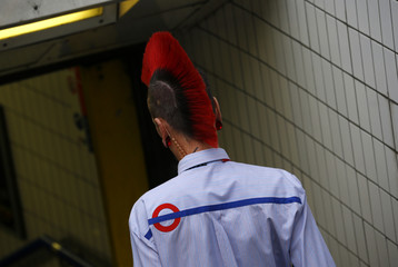 A London Underground worker with a mohawk enter Oxford Circus station shortly before the start of a 24 hour strike in London