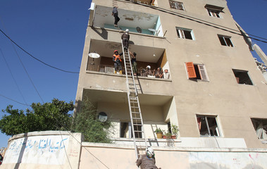 Civil defence members evacuate civilians from a building after airstrikes in Idlib city