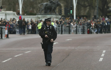 An armed police officer patrols a closed road during the Changing of the Guard ceremony at Buckingham Palace in London