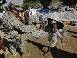 Cpt. John Godwin (L) of the 82nd Airborne is greeted by a Haitian boy at a tent encampment in Port-au-Prince