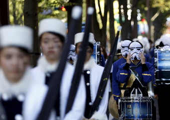 A member of a band puts on a Stormtrooper mask before a Star Wars parade, which is part of a Halloween parade in Kawasaki