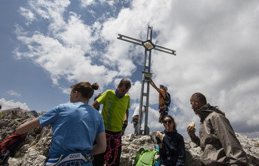 Climbers stand on the peak of Piz Da Lech in the Dolomite Mountains near the town of Corvara in northern Italy