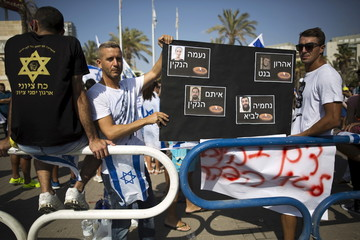 Israelis hold a placard depicting the pictures of Eitam and Na'ama Henkin who were shot dead on Thursday and Aharon Bennett and Nehemia Lavi who were  stabbed to death by a Palestinian man in Jerusalem's Old City on Saturday, during a protest  in the city