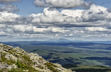 landscape Ural mountains, cliffs, rocks, sky with clouds and blue mountains in the background, tourism in Russia