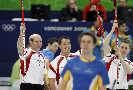 Canada's skip Martin, lead Hebert and second Kennedy celebrate their victory as a Sweden player leaves following their men's semifinal curling game at the Vancouver 2010 Winter Olympics