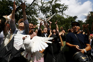 People release doves as symbol of peace at Yasukuni Shrine on the anniversary of Japan's surrender in World War Two in Tokyo