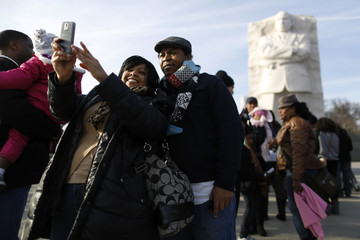Tomika Evans and Keith Gates take a picture of themselves during a visit the Martin Luther King Jr. Memorial on the U.S. national holiday in his honor, in Washington