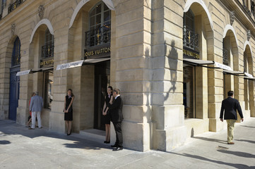 Hostess stand in front of the entrance of LVMH's Louis Vuitton's jewellery store on Place Vendome during its opening day in Paris