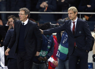 Paris St Germain's coach Laurent Blanc and Bayer Leverkusen's coach Sami Hyypia react at the end their Champions League round of 16 second leg soccer match at the Parc des Princes Stadium in Paris