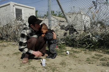 A refugee hugs a boy next to a border fence at a makeshift camp for migrants and refugees at the Greek-Macedonian border near the village of Idomeni