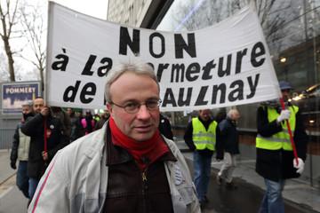 Jean-Pierre Mercier, CGT union representative at PSA Aulnay-sous-Bois automotive plant, stands near protest banner in Paris