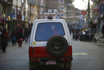 A woman sits behind in a vehicle as she travels along the streets of Kathmandu