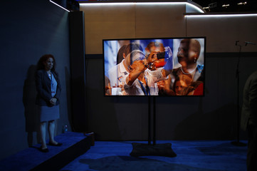 A sign language interpreter stands at the ready by a video screen on the floor during the first day of the Democratic National Convention in Philadelphia