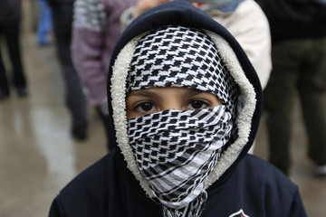 A Syrian boy with his face covered looks on during a protest against Syrian President Bashar al-Assad in the Damascus suburb of Saqba