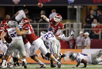Arkansas Wilson is hit by Kansas State Lamur as he passes the ball in the Cotton Bowl Classic football game in Arlington, Texas