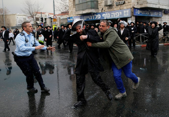 An undercover Israeli policeman detains an ultra-Orthodox Jewish protestor during a demonstration against members of their community serving in the Israeli army, part of ongoing demonstrations recently seen throughout Israel, in Jerusalem