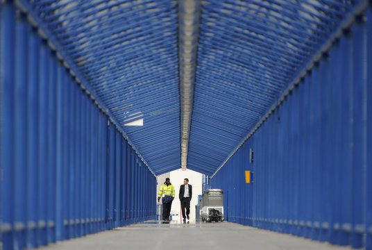 Two workers walk towards the car park at London City airport