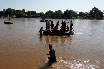 People arrive on a raft after crossing the Suchiate river, a natural border between Mexico and Guatemala, in Ciudad Hidalgo, Chiapas, Mexico