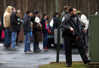 Police officer holds an automatic weapon as he stands near a building on the grounds of the Saint Rose of Lima Catholic church in Newtown, Connecticut