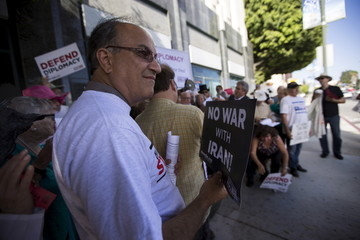 Activist and former political prisoner Pirzadeh holds a sign during a rally supporting the current Iran Nuclear Agreement in Los Angeles