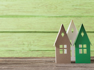 paper house on green wooden background