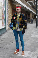 "Dales, a fashion blogger, poses outside the main catwalk venue for ""London Collections: Men"" in London"