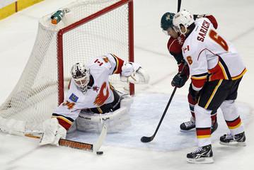 Calgary Flames goalie Miika Kiprusoff clears a shot by Minnesota Wild Devin Setoguchi during their NHL hockey game in St. Paul