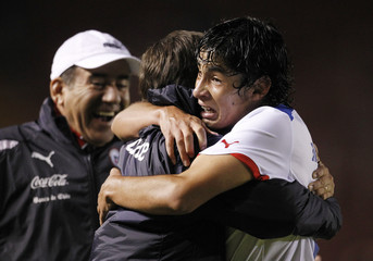 Chile's Marquez celebrates with head coach Vaccia and an assistant coach after he scored third goal against Venezuela during the Conmebol U-20 championship in Arequipa