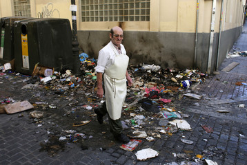 A man walks past garbage strewn on the pavement during almost a week of indefinite strike by street cleaners in central Madrid