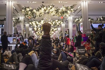 """A protester, demanding justice for Eric Garner, raises his fist in solidarity with others after they stage a """"die-in"""" at the Macy's department store in Herald Square, Manhattan, New York"""