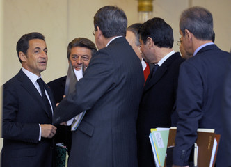 France's President Sarkozy speaks with members of the government following the weekly cabinet meeting at the ELysee Palace in Paris