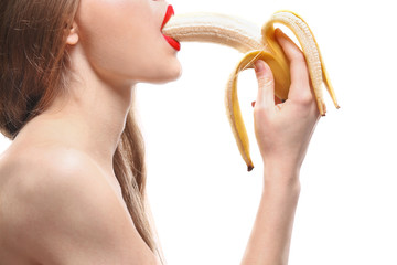 Beautiful woman with banana on white background