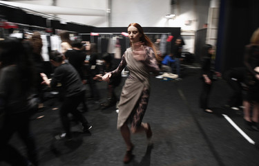 A model runs through the backstage to get changed during the Vivienne Tam Fall/Winter 2012 collection show during New York Fashion Week