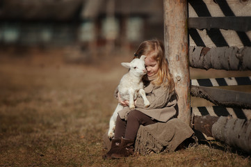 little girl with lamb on the farm. She sits by the fence and hugs the lamb. Fototapete