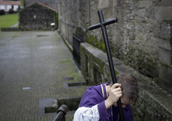 A young penitent waits to start the procession of the Santo Entierro brotherhood during Holy Week in Santiago de Compostela