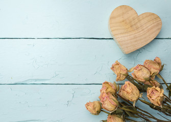 Love celebration background of dried peach roses and wooden carved heart isolated on rustic painted blue table