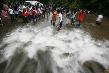 Students cross to a river to participate in the Feast of the Forest event at Cagueban town