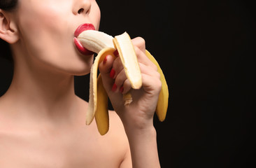 Sensual young woman eating banana on black background, closeup