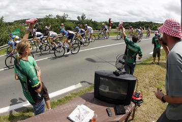 A pack of riders cycles past spectators during the 99th Tour de France cycling race between Rouen and Saint-Quenti