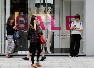 People walk past a fashion boutique in a shopping district in Tokyo