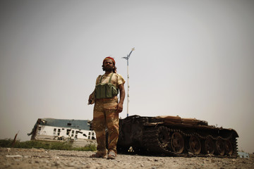 An army soldier stands near a tank destroyed during recent fighting between the army and al Qaeda-linked militants in Zinjibar