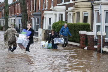 Residents carry their belongings through flood waters in the Warwick Road area of Carlisle, Britain