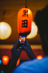 Young man making a picture of Japanese red lantern at night