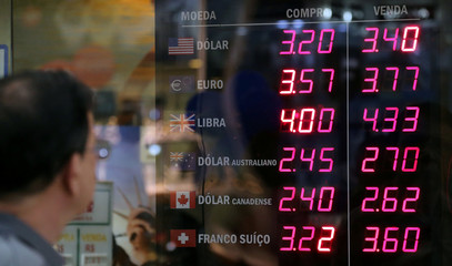Man observes a board showing the Brazilian Real-U.S. dollar and several other foreign currencies exchange rates in Rio de Janeiro