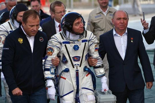 Russian cosmonaut Sergei Volkov, his father Soviet cosmonaut Aleksander Volkov and Roskosmos agency's head Igor Komarov go to board the Soyuz TMA-18M spacecraft at the Russian-leased Baikonur cosmodrome