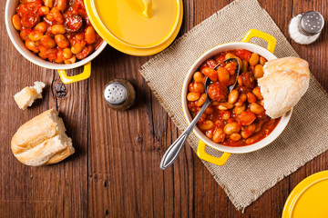 Baked beans in tomato sauce served in yellow, clay bowls.