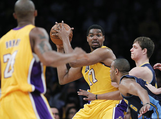 Lakers' Bynum looks to pass to teammate Bryant as he is double-teamed by the Nuggets during their NBA basketball game in Los Angeles