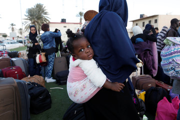 An African migrant girl is carried by her mother as they wait to be deported at Mitiga International Airport, east of Tripoli, Libya