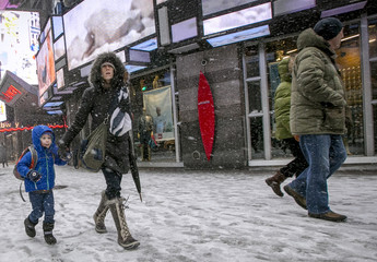 A young boy walks with his mother during a snow storm through Times Square in New York